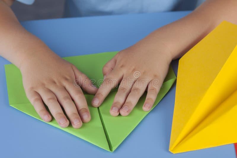 Enfant faisant un avion de papier images stock