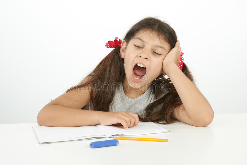 Enfant fatigué baîllant tandis qu'elle faisant son travail images libres de droits
