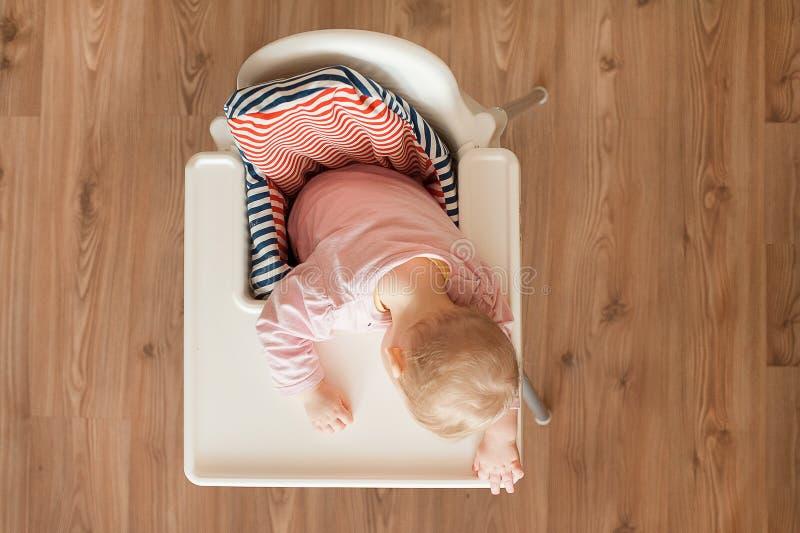 Enfant fatigué dormant dans le highchair après le déjeuner Bébé mignon girllying son visage sur le plateau de table Vue supérieur photos stock