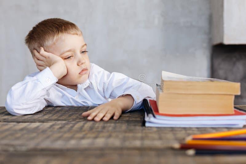 Enfant fatigué pas très enthousiaste au sujet de l'étude photo stock