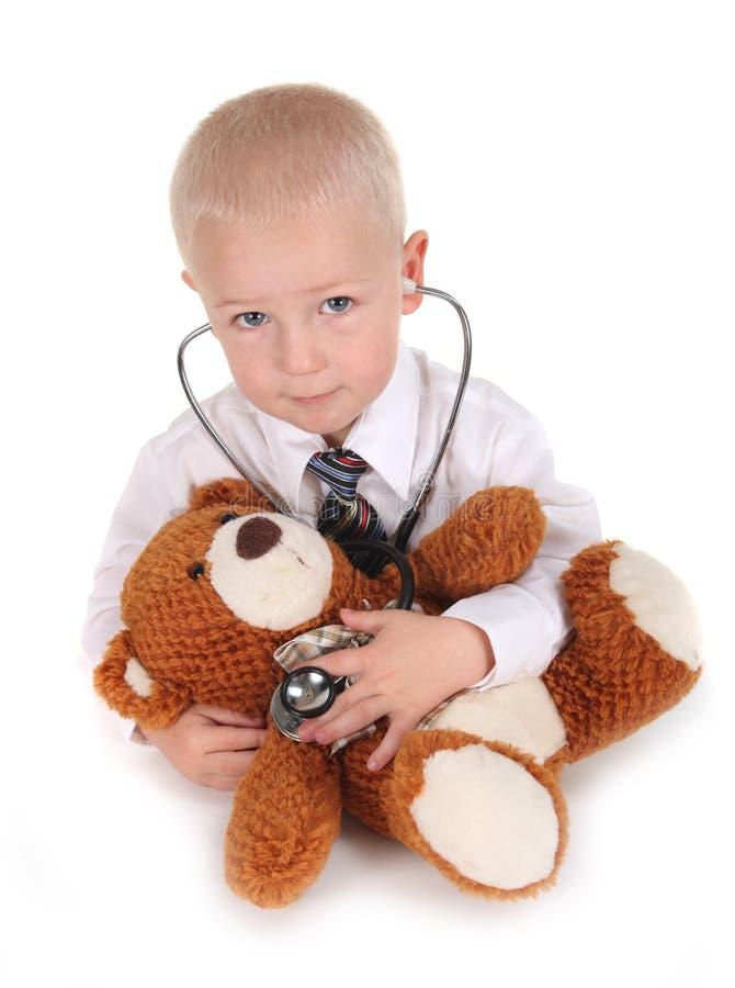 Enfant feignant pour être un ours de nounours de docteur With photo stock
