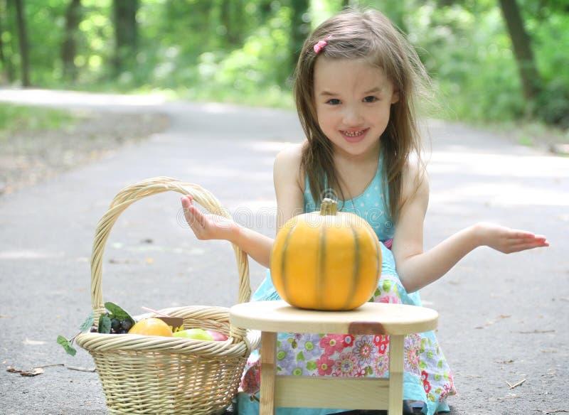 Enfant : Fille jouant avec Pumpking en stationnement photo libre de droits