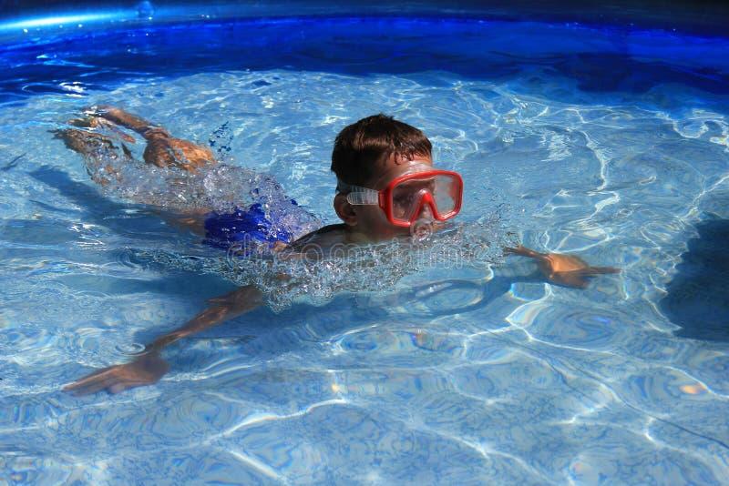 Enfant flottant dans la piscine photographie stock
