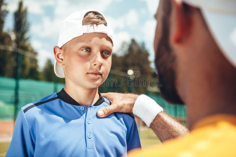Enfant focalisé parlant avec l'entraîneur image libre de droits