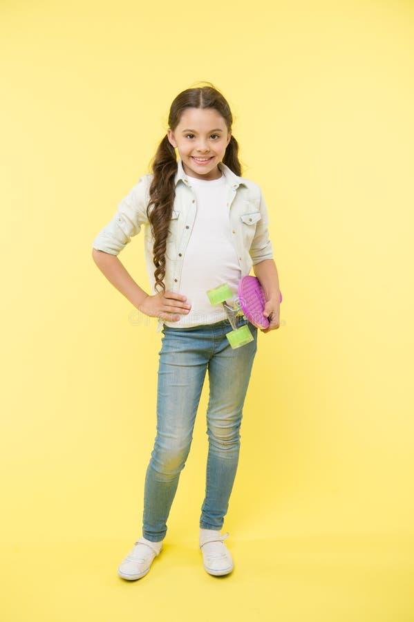 Enfant frais et goûts sûrs faisant de la planche à roulettes Joyeux et heureux Le style occasionnel de fille d'enfant avec le pan photo stock