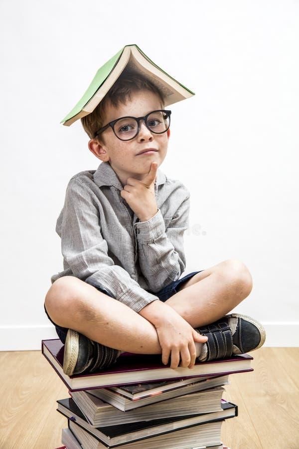 Enfant futé réfléchi avec le livre sur la tête ayant des pensées d'éducation image stock