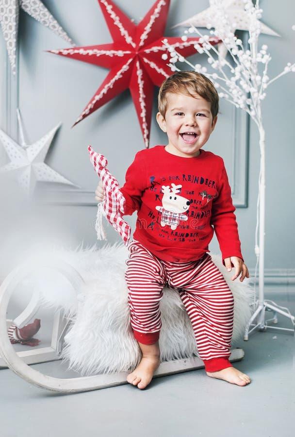 Enfant gai s'asseyant sur un traîneau de Noël photos stock