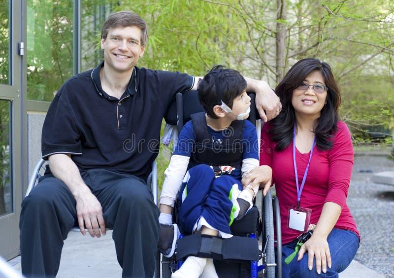 Enfant handicapé dans le fauteuil roulant avec ses parents image libre de droits