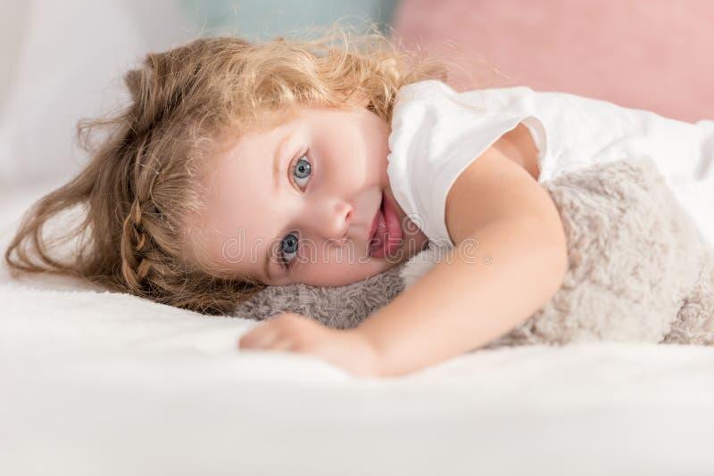 enfant heureux adorable grimaçant se trouvant sur le lit chez la pièce et le regard des enfants photographie stock libre de droits