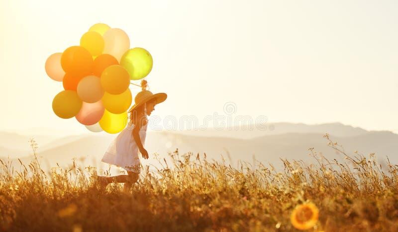 Enfant heureux avec des ballons au coucher du soleil en été photo stock
