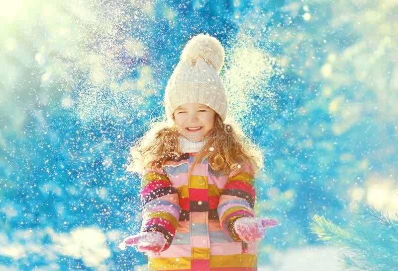 Enfant heureux ayant l'amusement jouant avec la neige en hiver image libre de droits