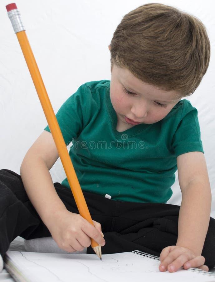 Enfant heureux colorant un livre image stock