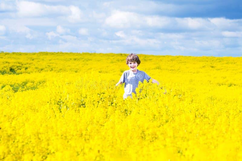 Enfant heureux courant dans un domaine des fleurs jaunes images libres de droits
