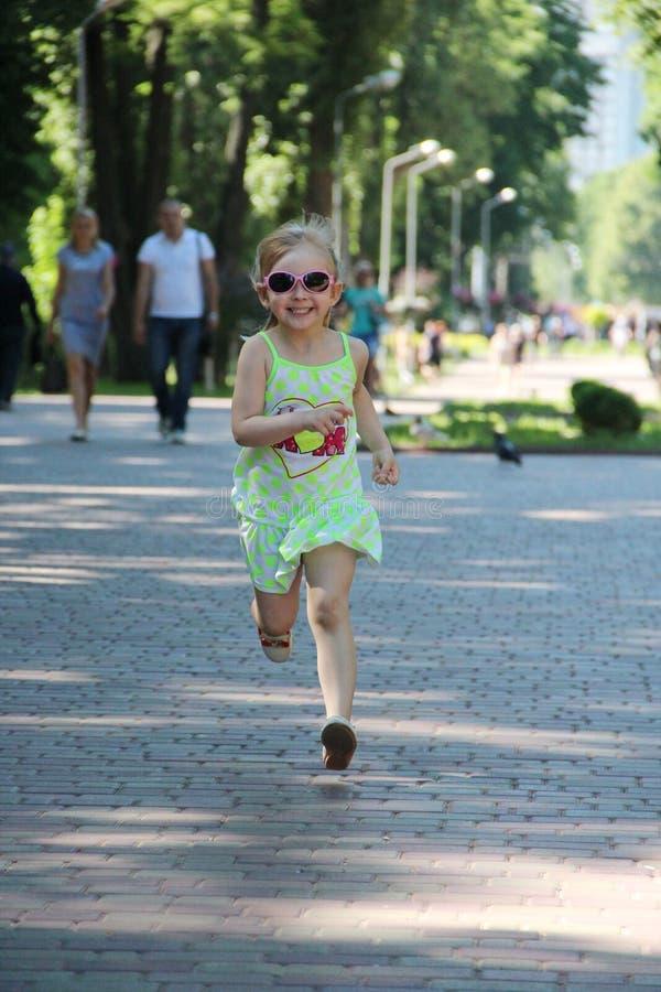 Enfant heureux courant en parc de ville Peu fille appr?ciant la course image stock