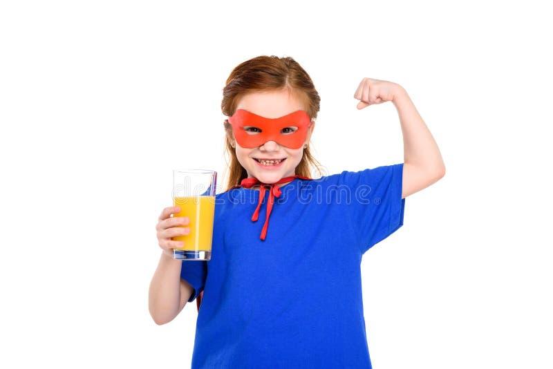 enfant heureux dans le costume de super héros tenant le verre de jus et montrant le biceps images libres de droits