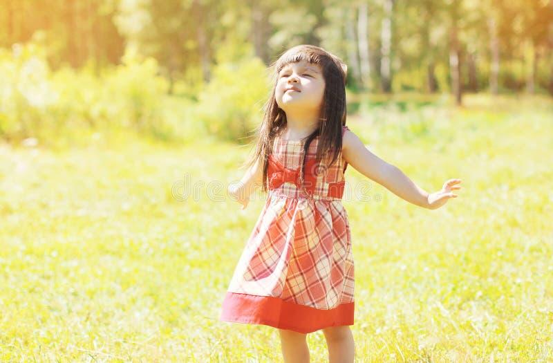 Enfant heureux de petite fille appréciant dehors le ressort ensoleillé chaud photo stock