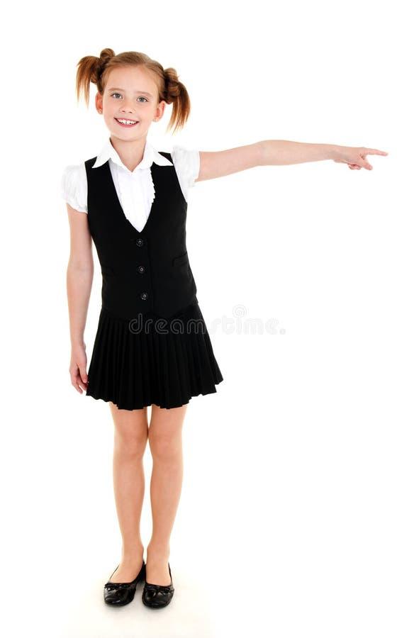 Enfant heureux de sourire de fille d'école dans l'uniforme montrant vers la droite image stock