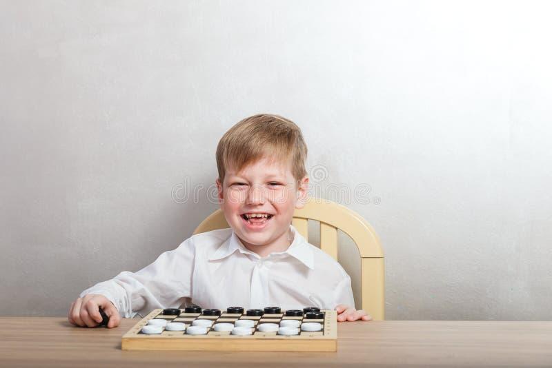 Enfant heureux gai jouant des contrôleurs à la table photographie stock
