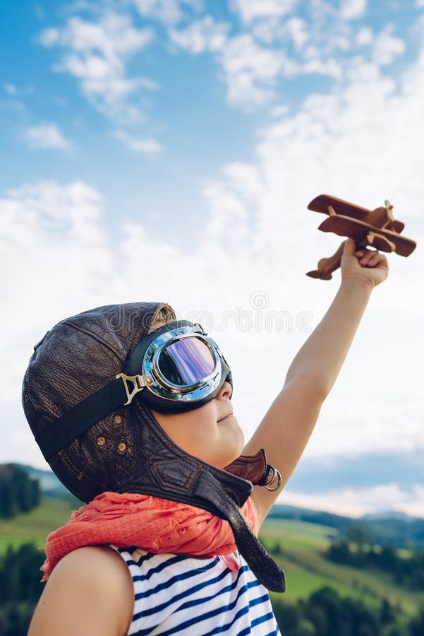 Enfant heureux jouant avec l'avion en bois de jouet contre l'été bleu s photos stock
