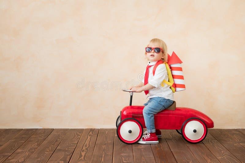 Enfant heureux jouant avec la fus?e de jouet ? la maison photo libre de droits