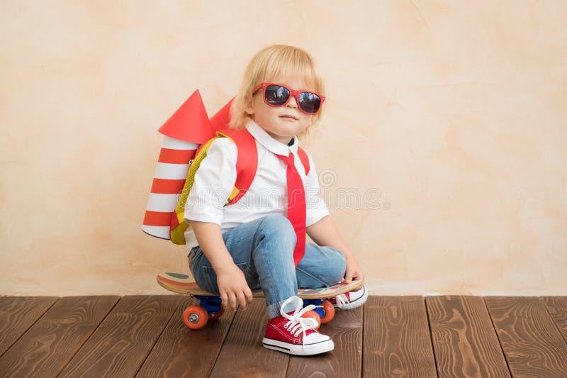 Enfant heureux jouant avec la fus?e de jouet ? la maison image stock