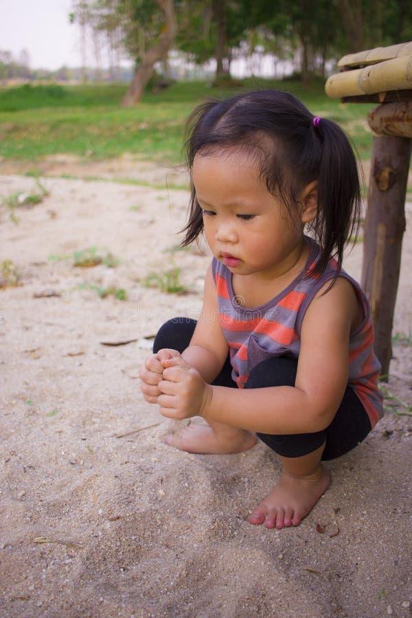 Enfant heureux jouant avec le sable, famille asiatique drôle en parc photographie stock libre de droits