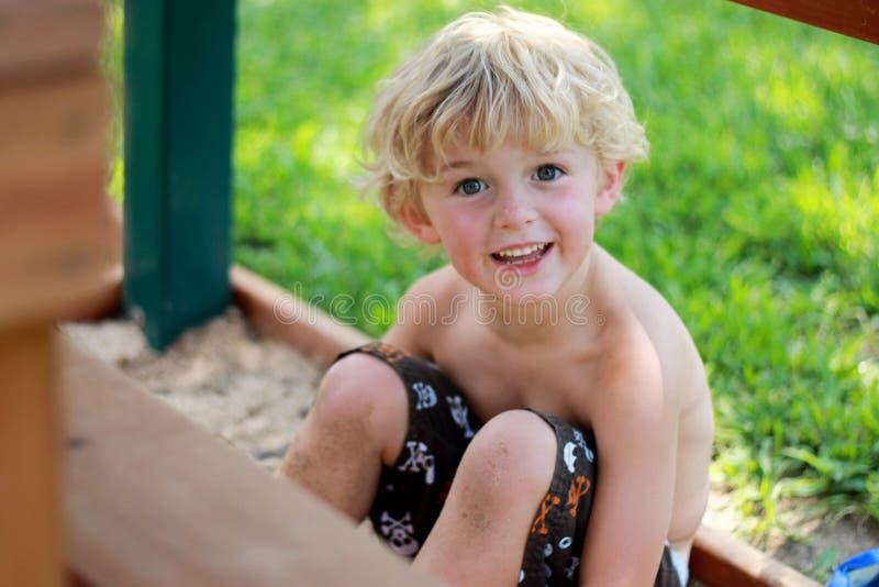 Enfant heureux jouant dans la boîte de sable photos stock