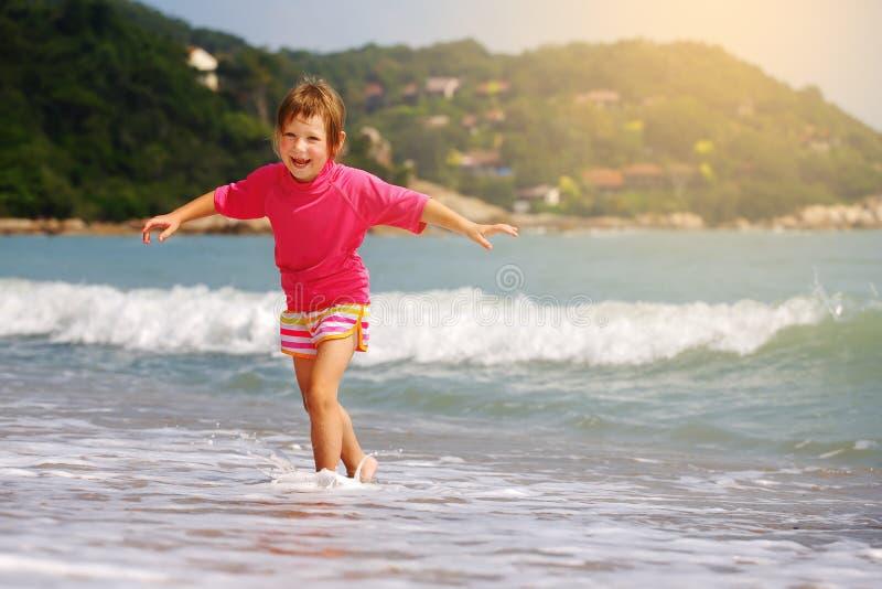 Enfant heureux jouant en mer image stock