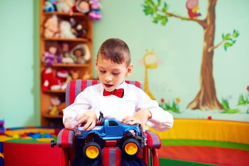 Enfant heureux mignon sur le fauteuil roulant avec le présent dans le jardin d'enfants pour des enfants avec les besoins spéciaux image stock