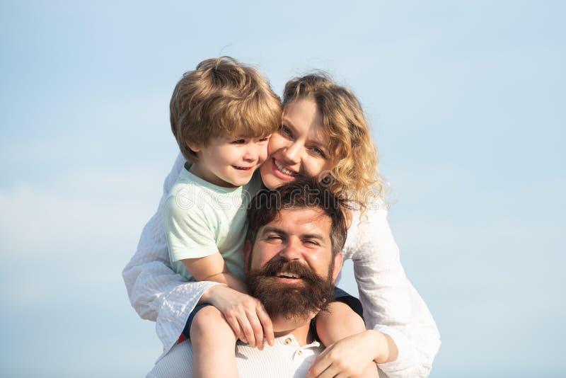 Enfant heureux montrant à ses parents l'avion de papier Adoptez l'enfant parenthood Garçon de sourire heureux sur le papa d'épaul photos libres de droits