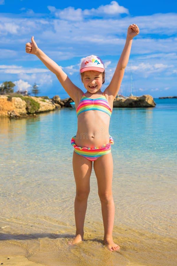 Enfant heureux montrant des pouces sur la plage photographie stock
