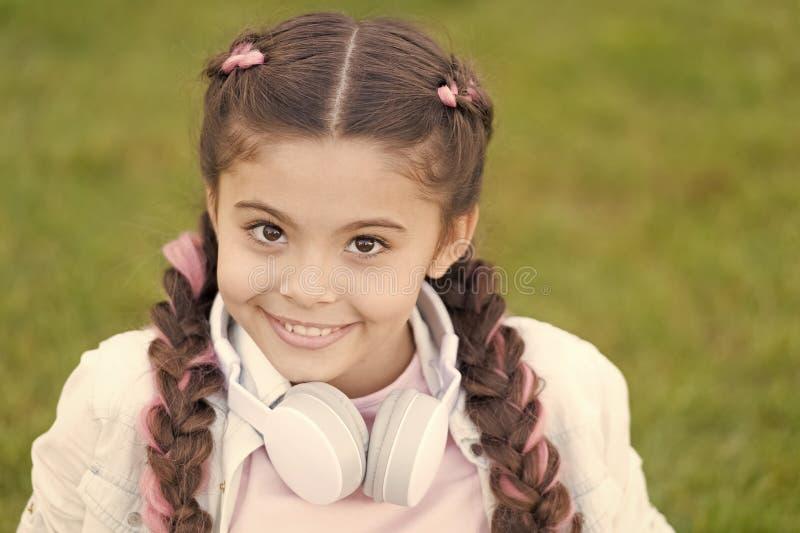 Enfant heureux ?motif en bonne sant? d?tendant dehors Ce qui rend l'enfant heureux La coiffure de tresses de fille et les ?couteu image stock