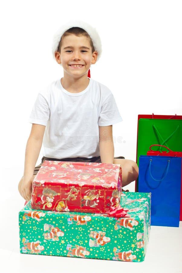 Enfant heureux s'asseyant avec des cadeaux de Noël photographie stock