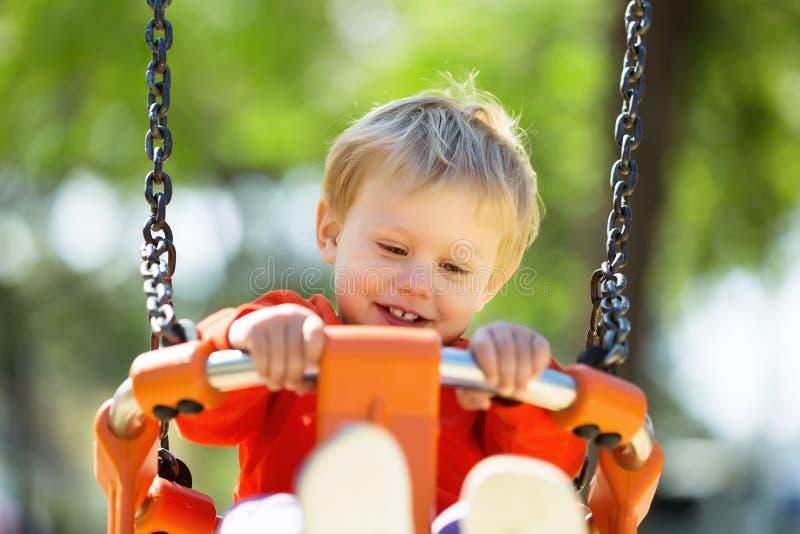 Enfant heureux sur l'oscillation orange photos stock