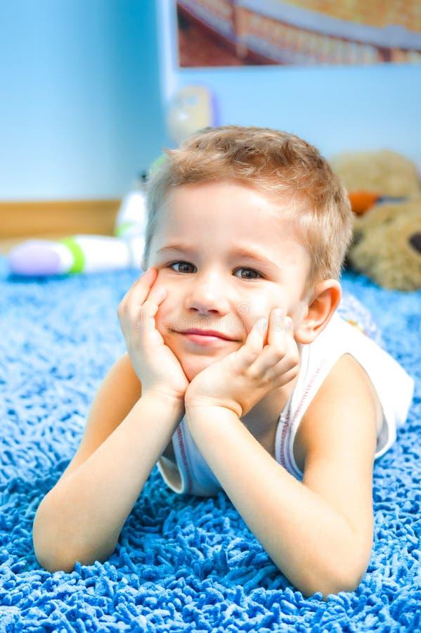 Enfant heureux sur le plancher dans le salon à la maison image stock