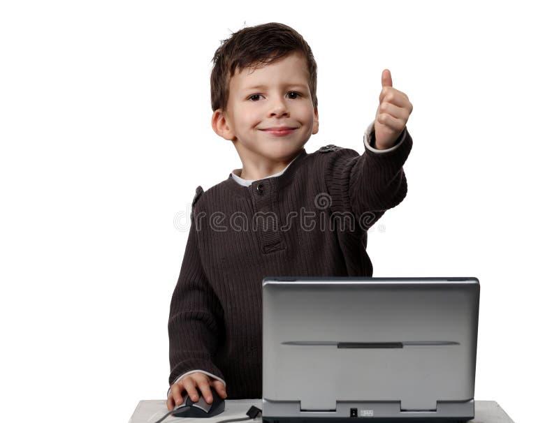 Enfant heureux travaillant sur l'ordinateur portatif avec des pouces vers le haut photos libres de droits