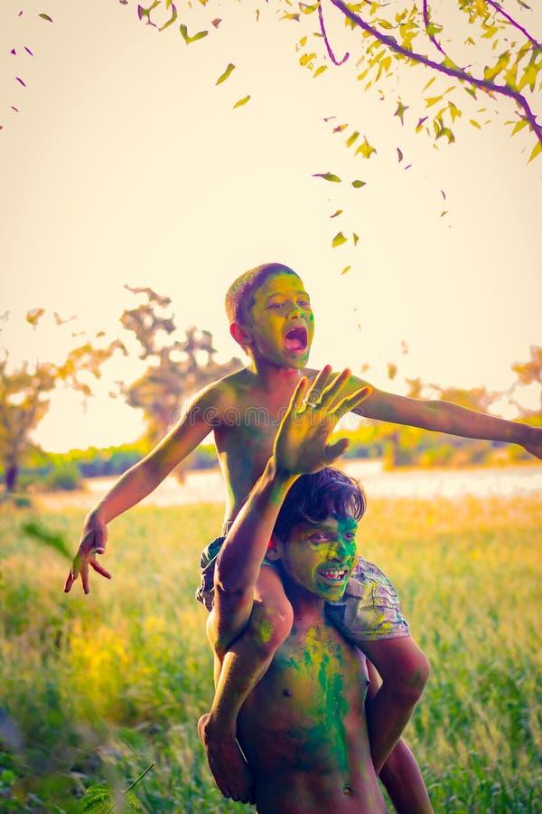 Enfant indien jouant avec la couleur dans le festival de holi photos libres de droits