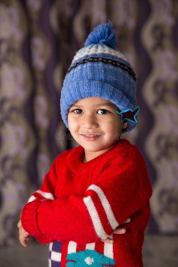Enfant indien mignon frappant une pose dans l'usage d'hiver avec un sourire mignon image stock