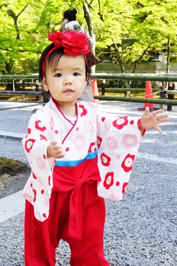 Enfant japonais en tenue traditionnelle, fête des cerisiers en fleurs image stock