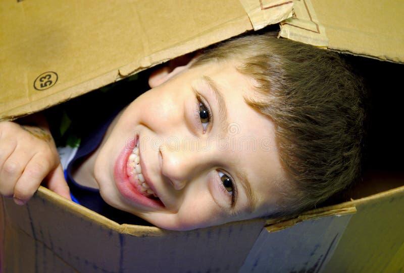 Enfant jetant un coup d'oeil hors d'un cadre image libre de droits
