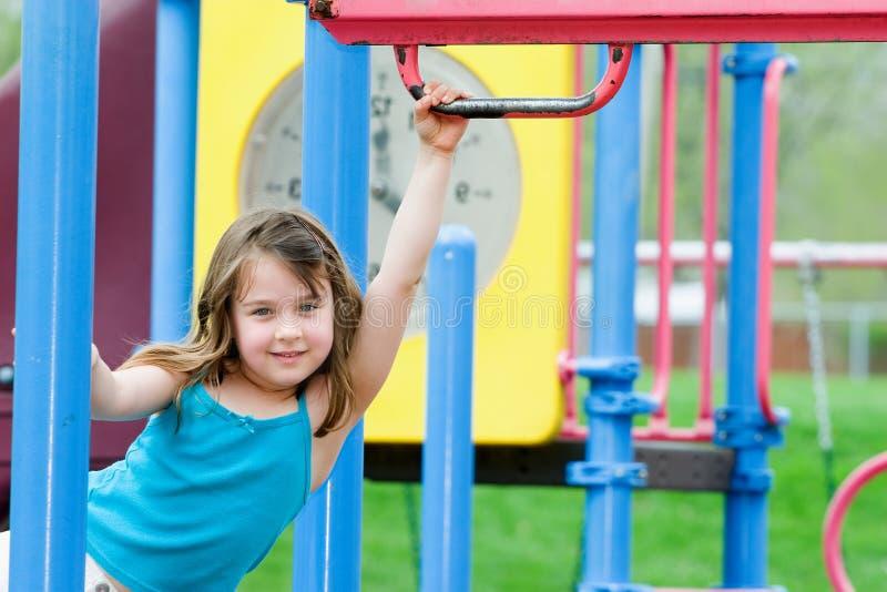 Enfant jouant à la cour de jeu photos stock