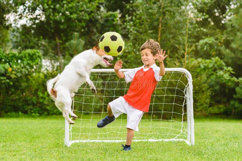 Enfant jouant au football du football comme gardien de but effrayé du vol de boule après tir d'en-tête images stock