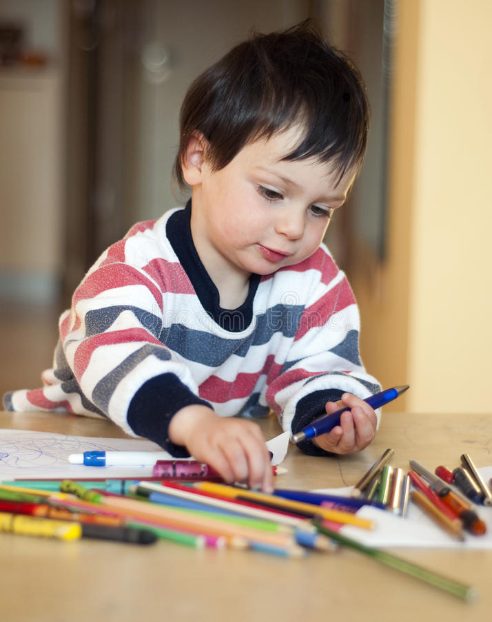 Enfant jouant avec des crayons photo stock