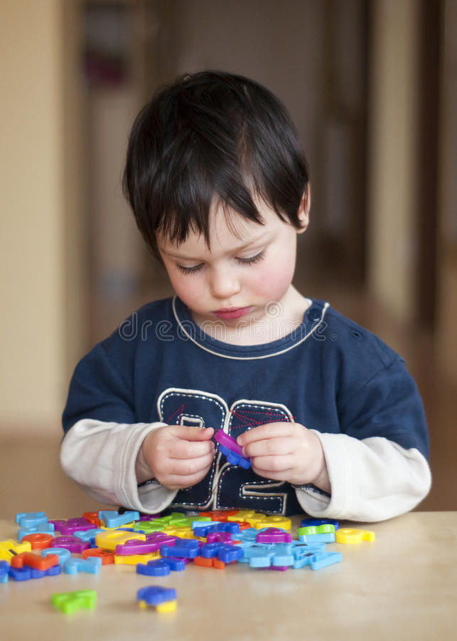 Enfant jouant avec des lettres images stock