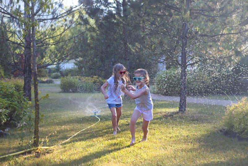 Enfant jouant avec l'arroseuse de jardin Les enfants courent et sautent Amusement extérieur de l'eau d'été dans l'arrière-cour images stock