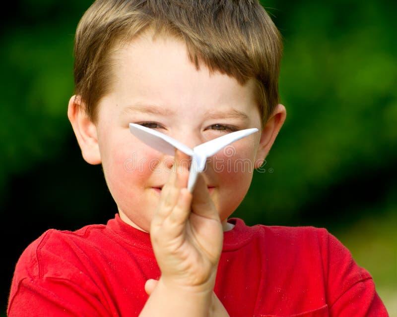 Enfant jouant avec l'avion de papier images stock