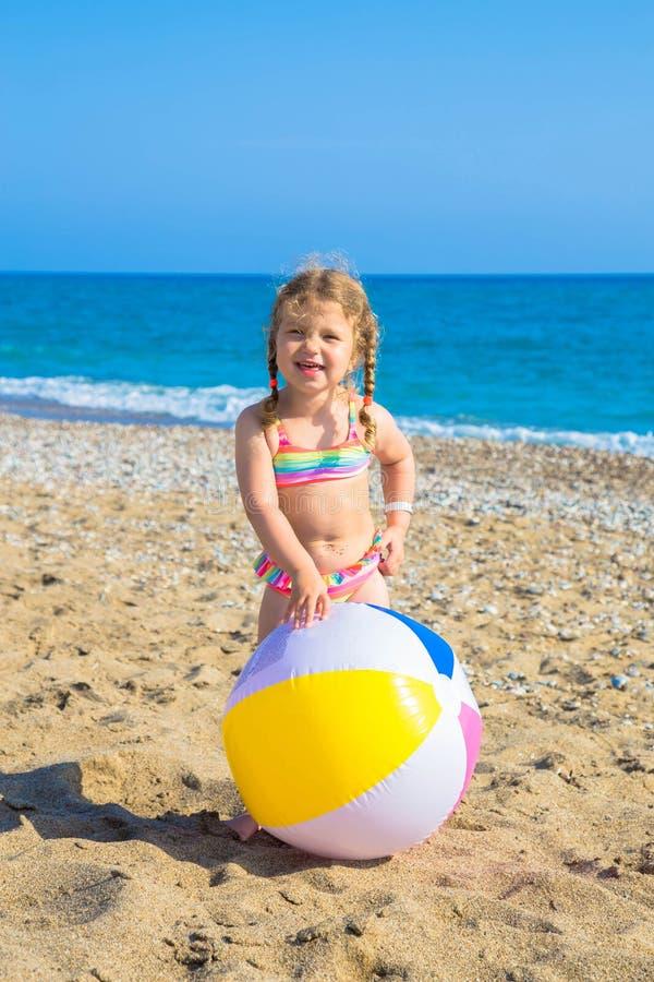 Enfant jouant avec la boule sur la plage photographie stock