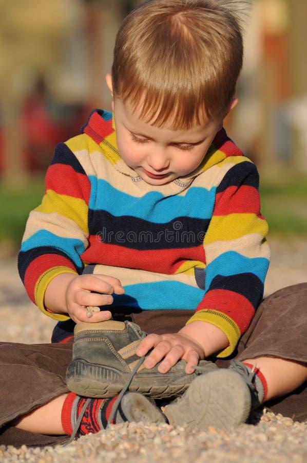 Enfant jouant avec la chaussure images stock
