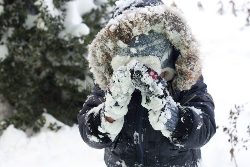 Enfant jouant avec la neige image stock