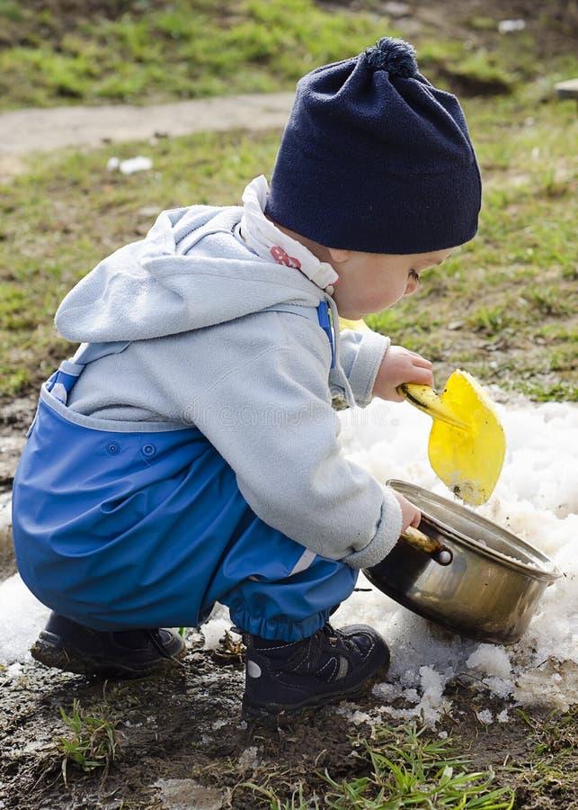 Enfant jouant avec la neige au printemps photos stock